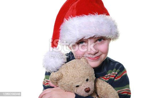 istock Boy Cuddling Teddy Bear, Wearing Santa Hat 1289256346