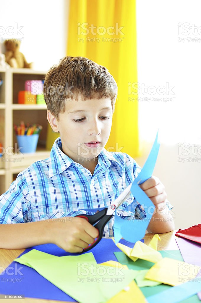 Boy cutting colored paper stock photo