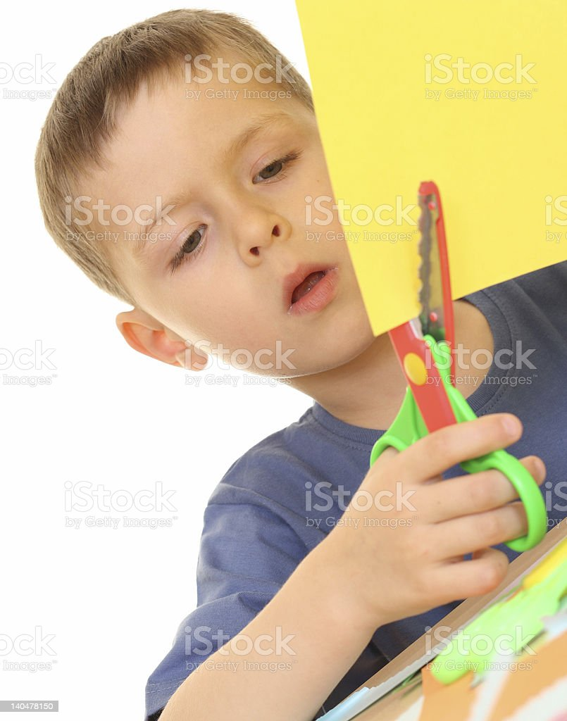 A boy cutting yellow paper with red and green scissors royalty-free stock photo