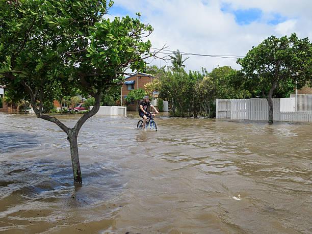 Boy Cycling through Flood Waters stock photo
