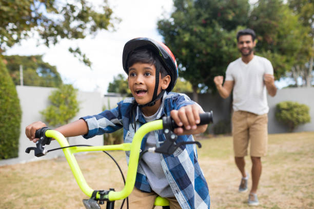 Boy cycling with father standing in background stock photo