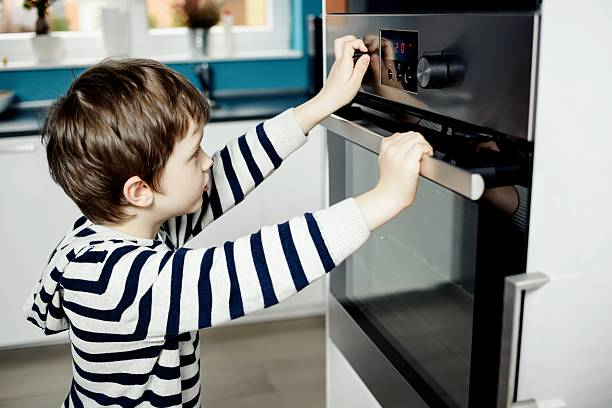 Boy dangerously playing with the knobs on the oven stock photo