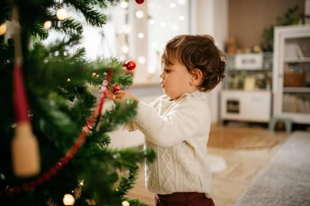 Boy decorating a christmas tree stock photo
