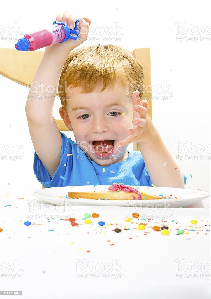 Boy decorating baked biscuits royalty-free stock photo