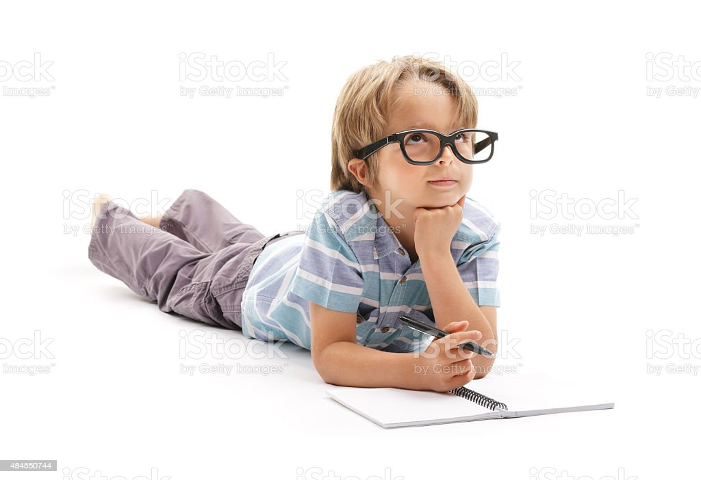 Boy deep in thought doing homework stock photo