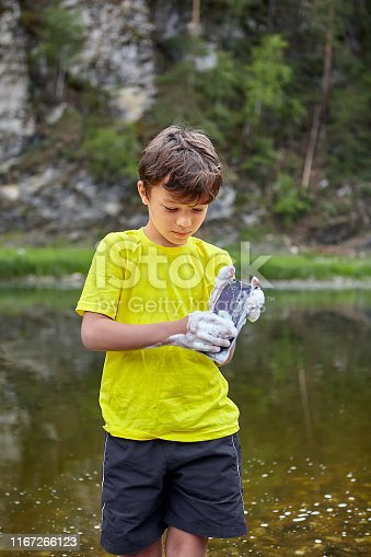 Little bully is washing his parents cellphone by soap, he is standing near river in forest.