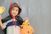 istock boy devil smile and playing paper ghost 1060519258