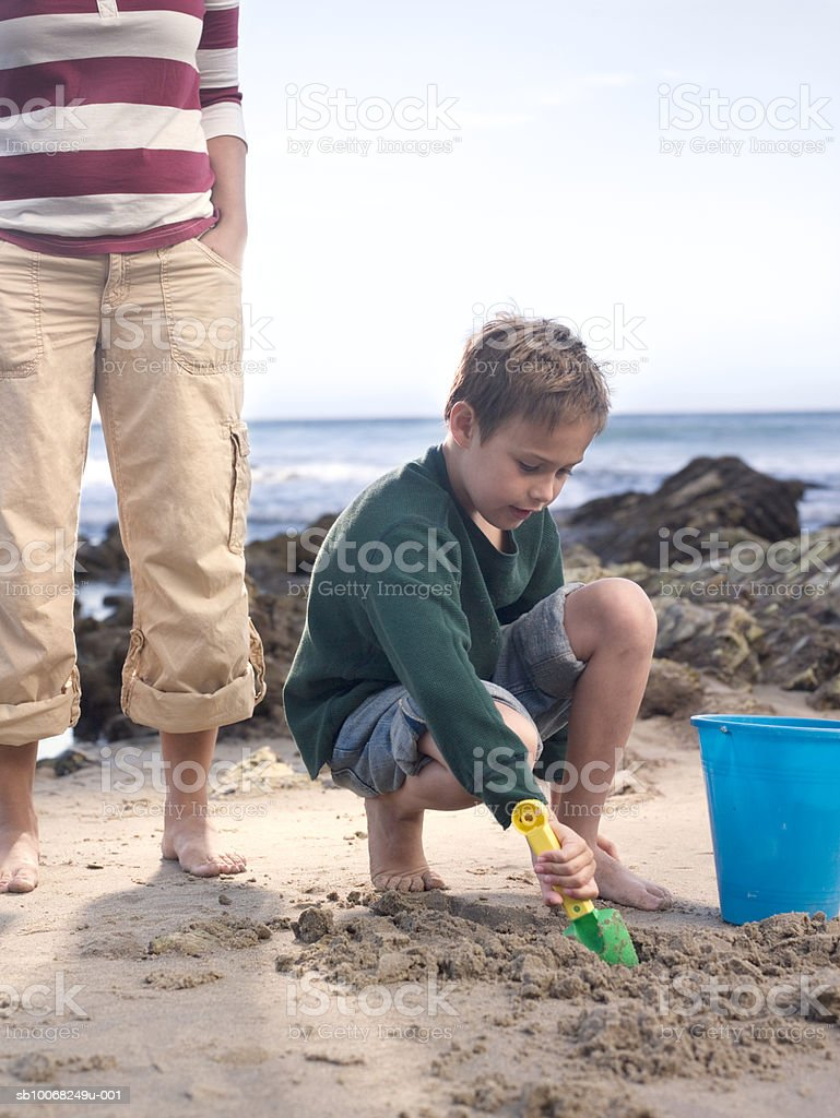 Boy (6-7) digging in sand on beach, mother standing behind royalty-free stock photo