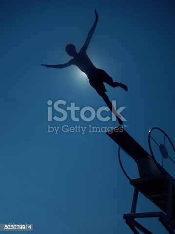 boy jumping to sea from diving board