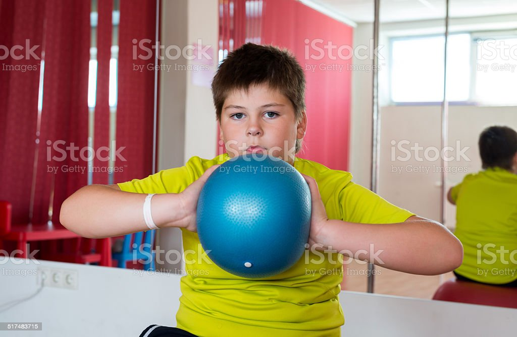 Boy does exercise with the ball stock photo