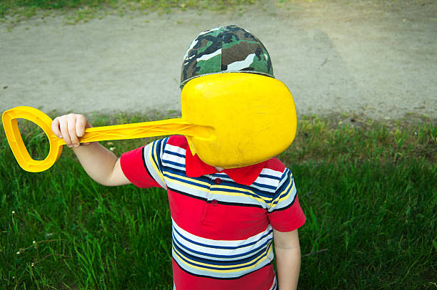 Boy does not want to be photographed Boy covered his face with a shovel disavow stock pictures, royalty-free photos & images
