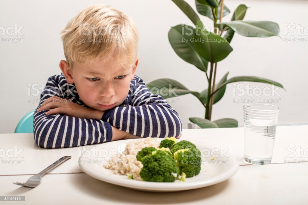 Boy does not want to eat his veggies stock photo