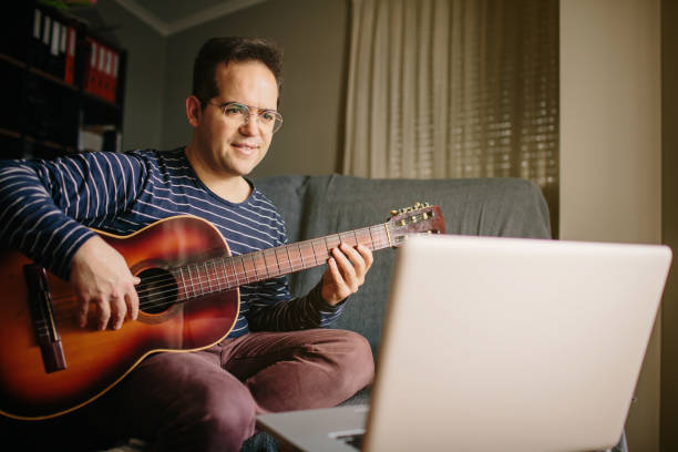 Boy doing an online course to learn how to play the classical guitar. He is sitting on the sofa at home, playing the guitar in front of the laptop while listening to the lessons