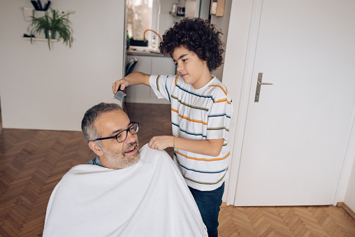 Son cutting his father's hair at home.