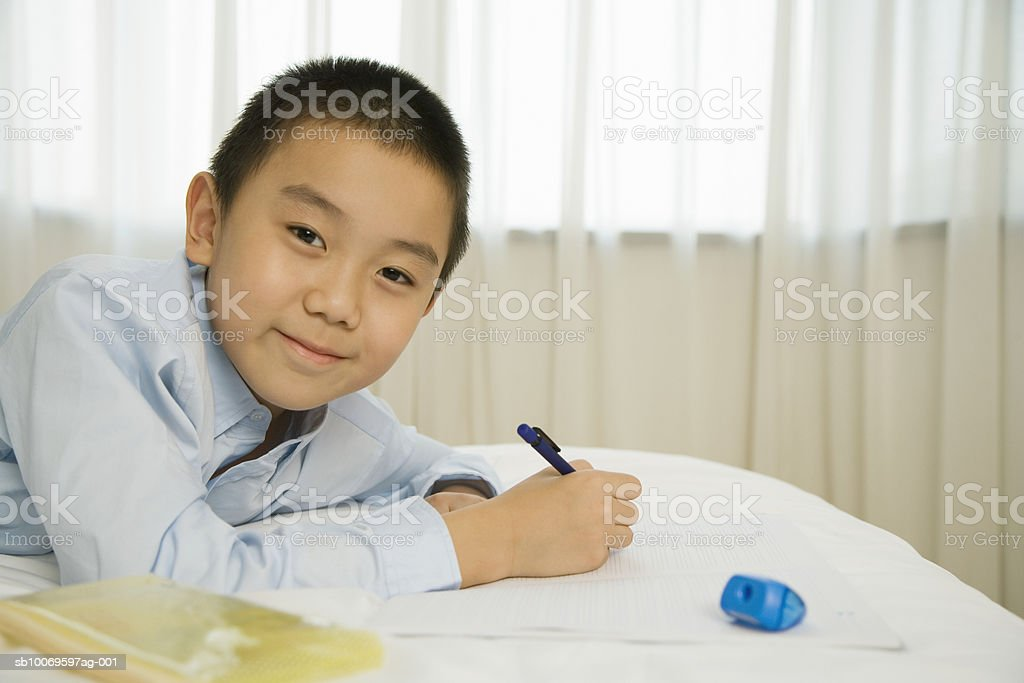 Boy (8-9) doing his homework, smiling, portrait royalty-free stock photo