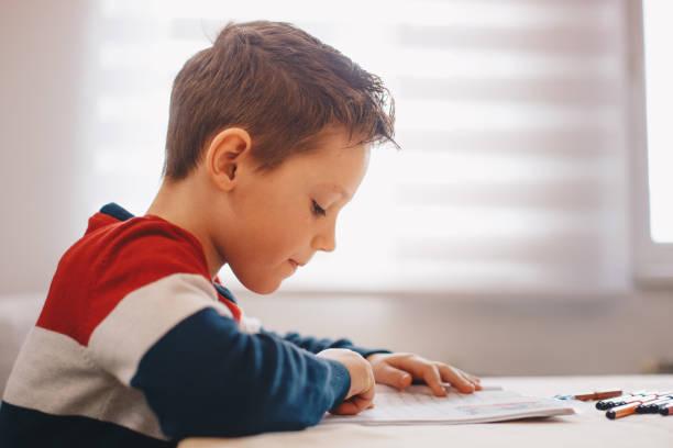 menino que faz seu trabalho ou trabalhos de casa da escola - reading - fotografias e filmes do acervo