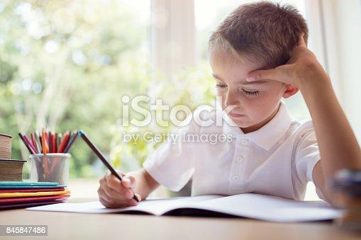istock Boy doing his school work or homework 845847486