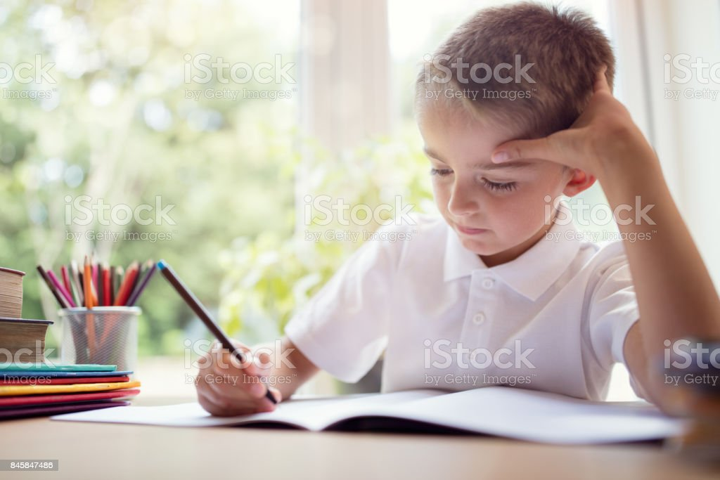 Boy doing his school work or homework stock photo
