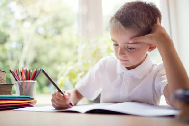 boy doing his school work or homework - writing class stock photos and pictures