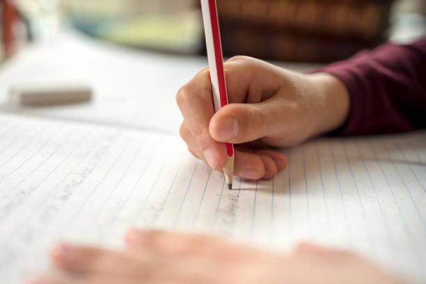 мальчик делает свою школьную работу или домашнее задание - писать стоковые фото и изображения