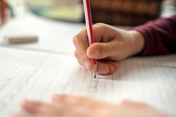 Boy doing his school work or homework Boy writing in a notepad doing his school work spelling or homework schoolboy stock pictures, royalty-free photos & images
