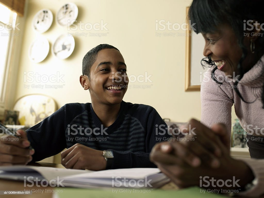 Boy (12-13) doing homework at kitchen table, mother assisting royalty-free stock photo