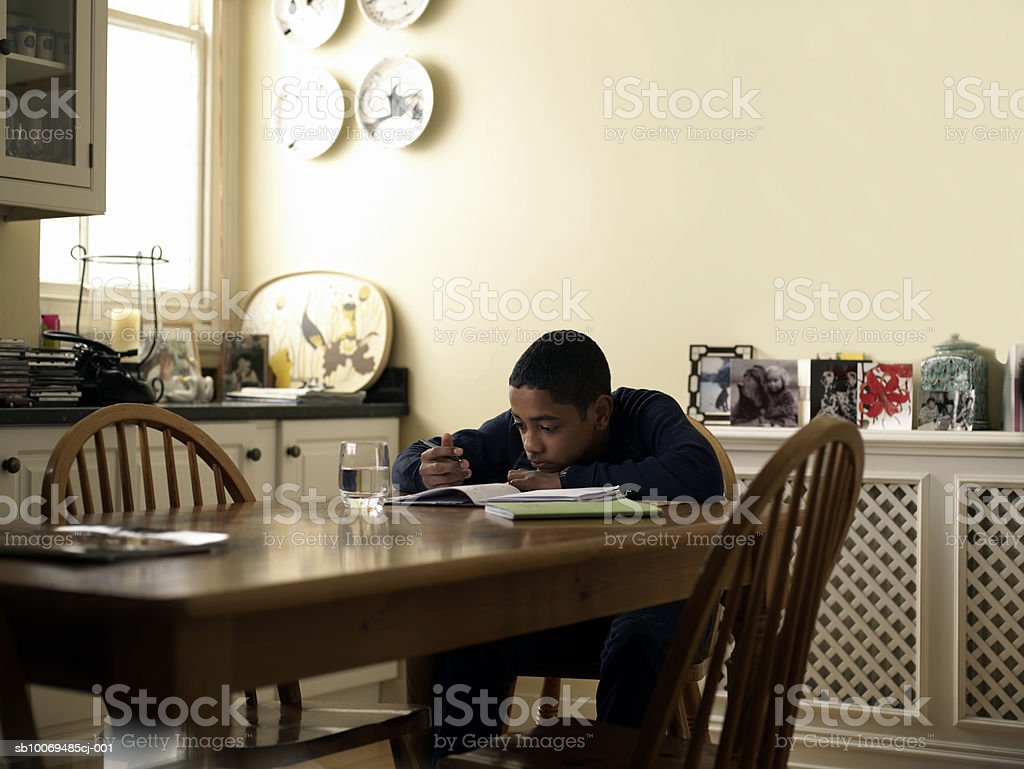 Boy (12-13) doing homework at kitchen table royalty free stockfoto