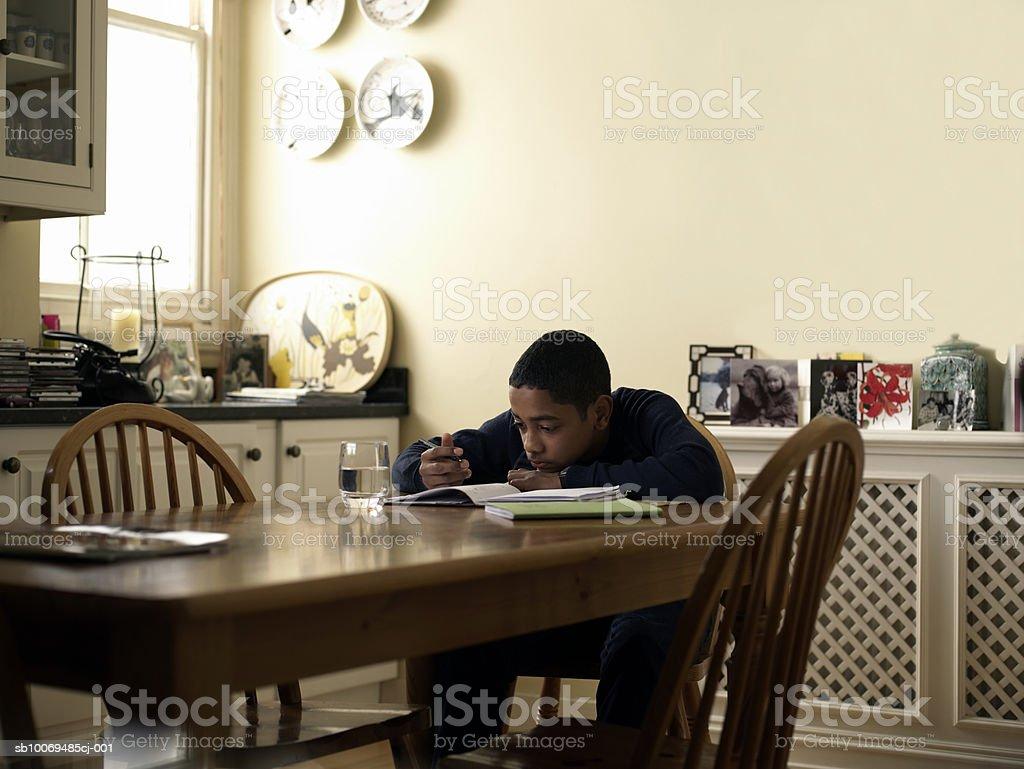 Menino (12-13) a fazer trabalho de casa com mesa de cozinha foto de stock royalty-free