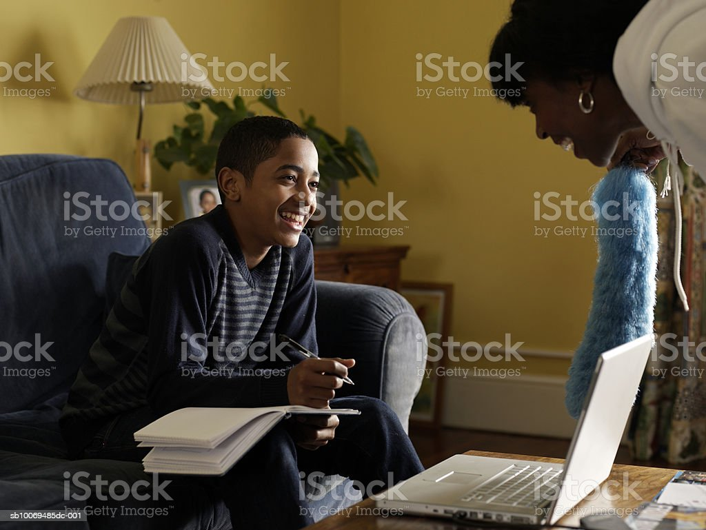 Boy (12-13) doing homework in living room, smiling to mother royalty-free stock photo