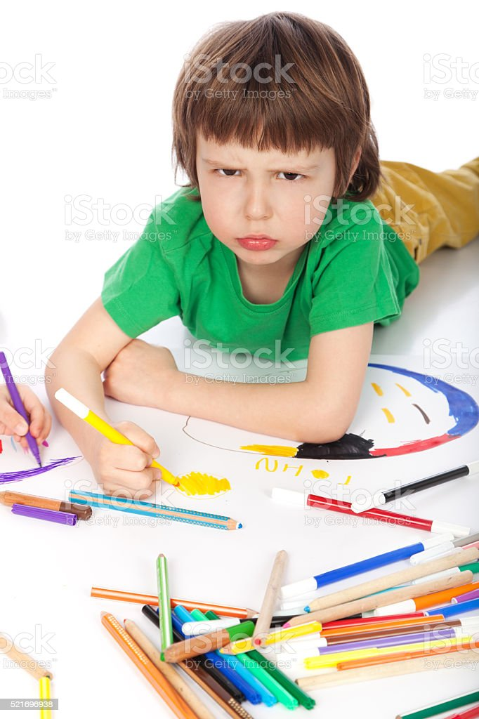 Boy doodling on white paper stock photo