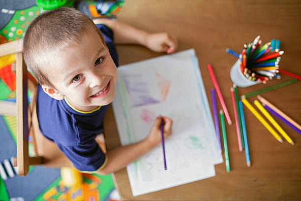 boy, drawing a picture for mum and dad - kids drawing stok fotoğraflar ve resimler