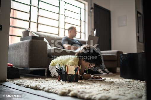 Boy drawing and his father working on background at home