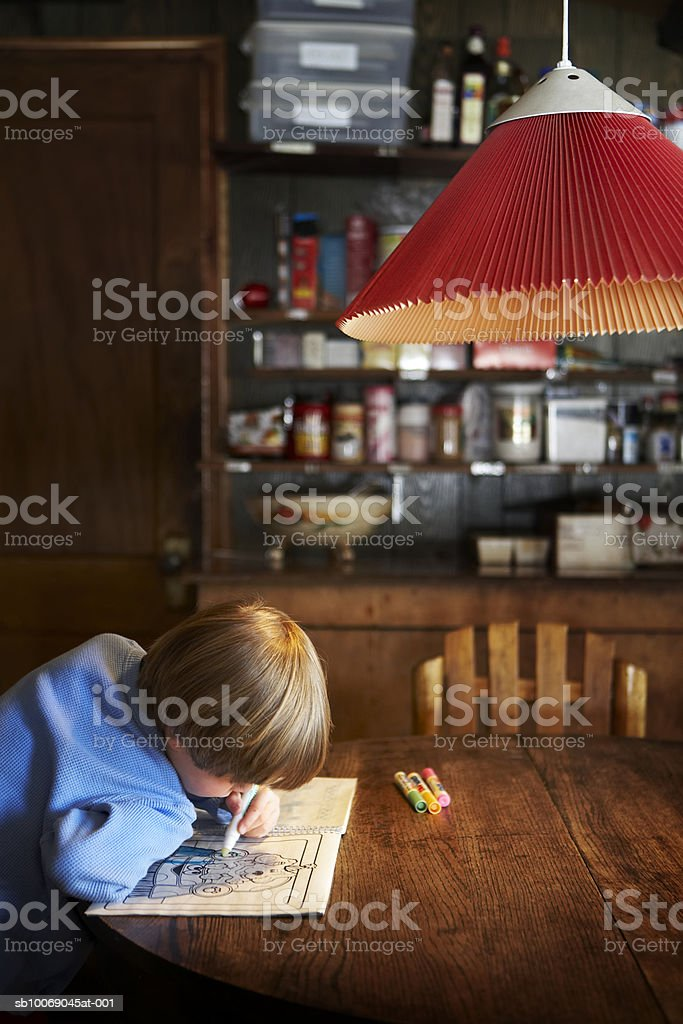 Boy (4-5) drawing on book royalty-free stock photo