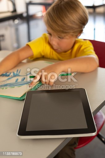 655532196 istock photo Boy drawing sketch on notebook at desk in a classroom 1133785573