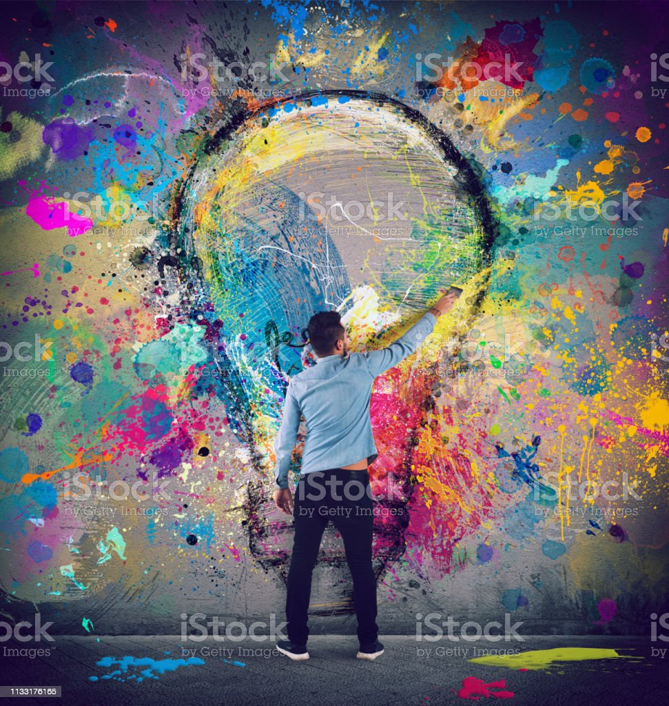 Boy draws with a brush a big light bulb. Concept of innovation and creativity Boy draws with a brush an abstract big light bulb. Concept of innovation and creativity Adult Stock Photo
