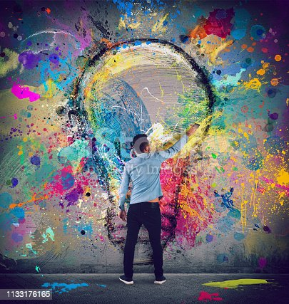 istock Boy draws with a brush a big light bulb. Concept of innovation and creativity 1133176165