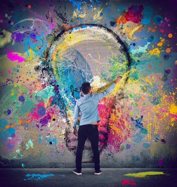 junge zeichnet mit einem pinsel eine große glühbirne. innovationskonzept und kreativität - innovation stock-fotos und bilder