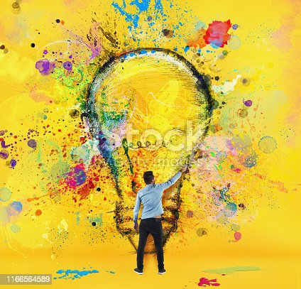 Boy draws with a brush an abstract big light bulb. Concept of innovation and creativity. Yellow style