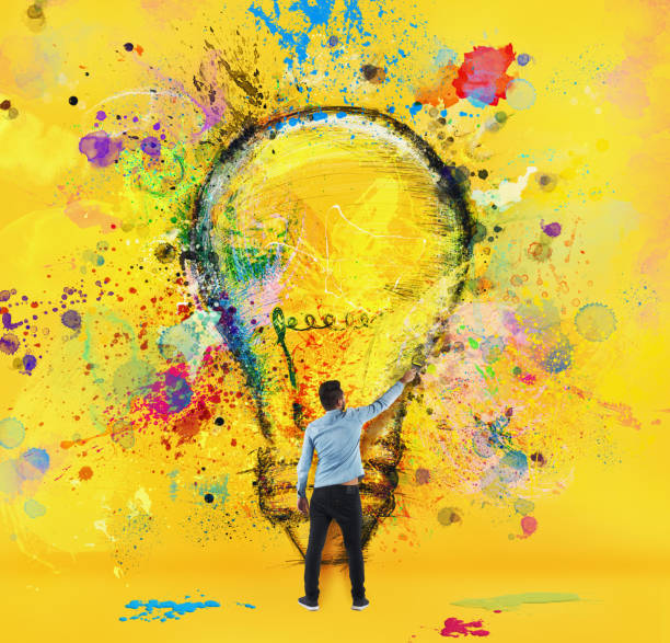 Boy draws with a brush a big light bulb. Concept of innovation and creativity. Yellow style - foto stock