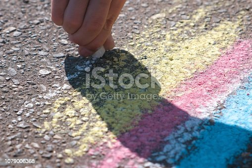 istock Boy draws with blue chalk on the asphalt. Close-up hands. 1079006368