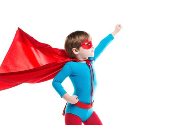Boy dreamer in a superhero costume, blue bodysuit and red cloak. stock photo