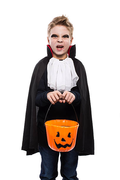 junge gekleidet als vampir und hältst eine kürbis-korb - kleine jungen kostüme stock-fotos und bilder