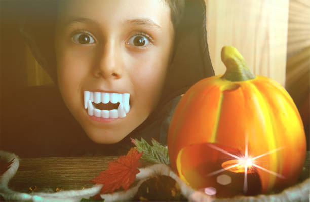 Boy (6-7) dressed as vampire with vampire teeth. Portrait of a child  on a Halloween background with eerie, dramatic light. Halloween concept. Halloween Pumpkin and decorations. Boy (6-7) dressed as vampire with vampire teeth. Portrait of a child  on a Halloween background with eerie, dramatic light. Halloween concept. Halloween Pumpkin and decorations. fang stock pictures, royalty-free photos & images