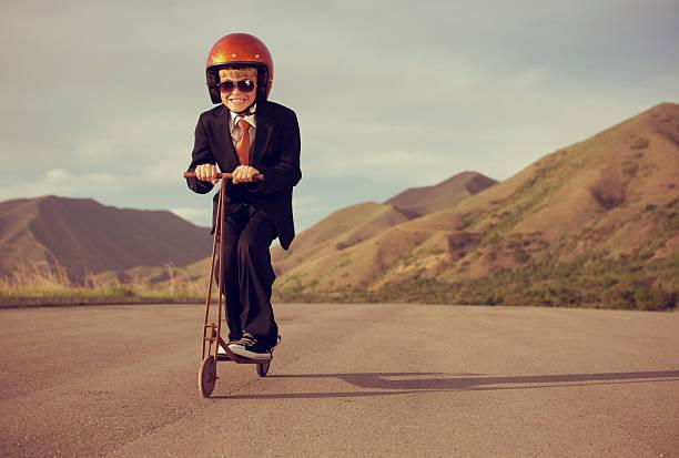 junge gekleidet im business-anzug auf retro roller - kinder die schnell arbeiten stock-fotos und bilder