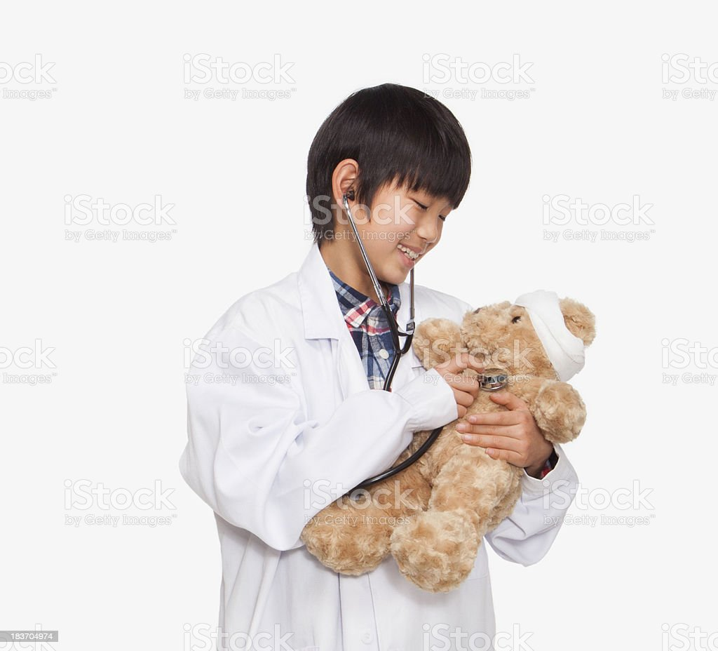 Boy dressed up as doctor checking teddy bear's vital signs stock photo