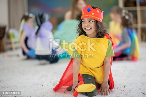 A boy with long hair of Indian descent smiles as he sticks out his sword that goes along with his king's costume. He is on a carpet in a colourful elementary school classroom.