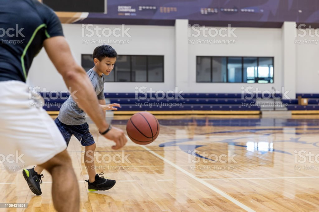 A young elementary age boy dribbles a basketball past his...
