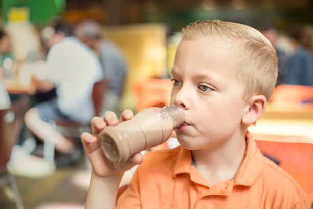 Boy drinking chocolate milk during lunch at his school cafeteria Cute boy drinking a bottle of chocolate milk during school lunch at his elementary school cafeteria. Healthy eating habits being taught at the public school system chocolate milk stock pictures, royalty-free photos & images