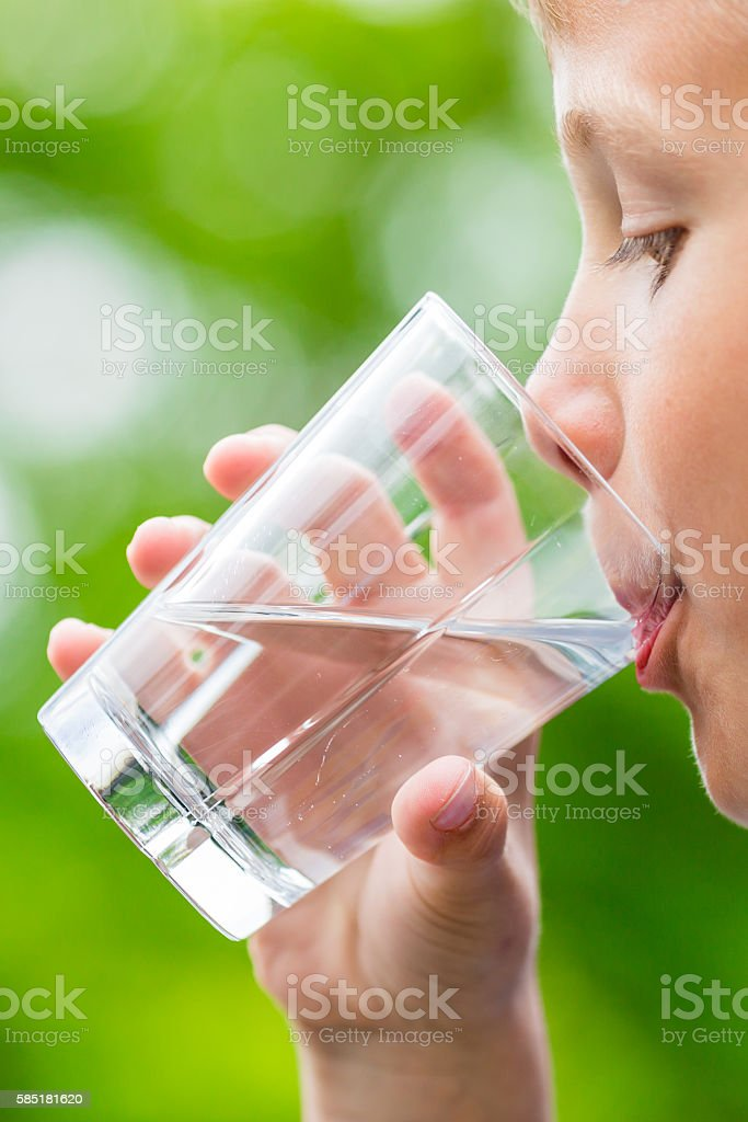 Close-up of young scandinavian child drinking fresh and pure tap...