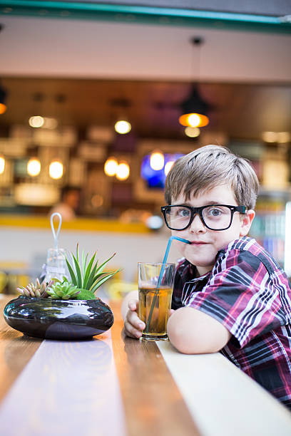 boy drinking juice. - nerd boy eating stock photos and pictures
